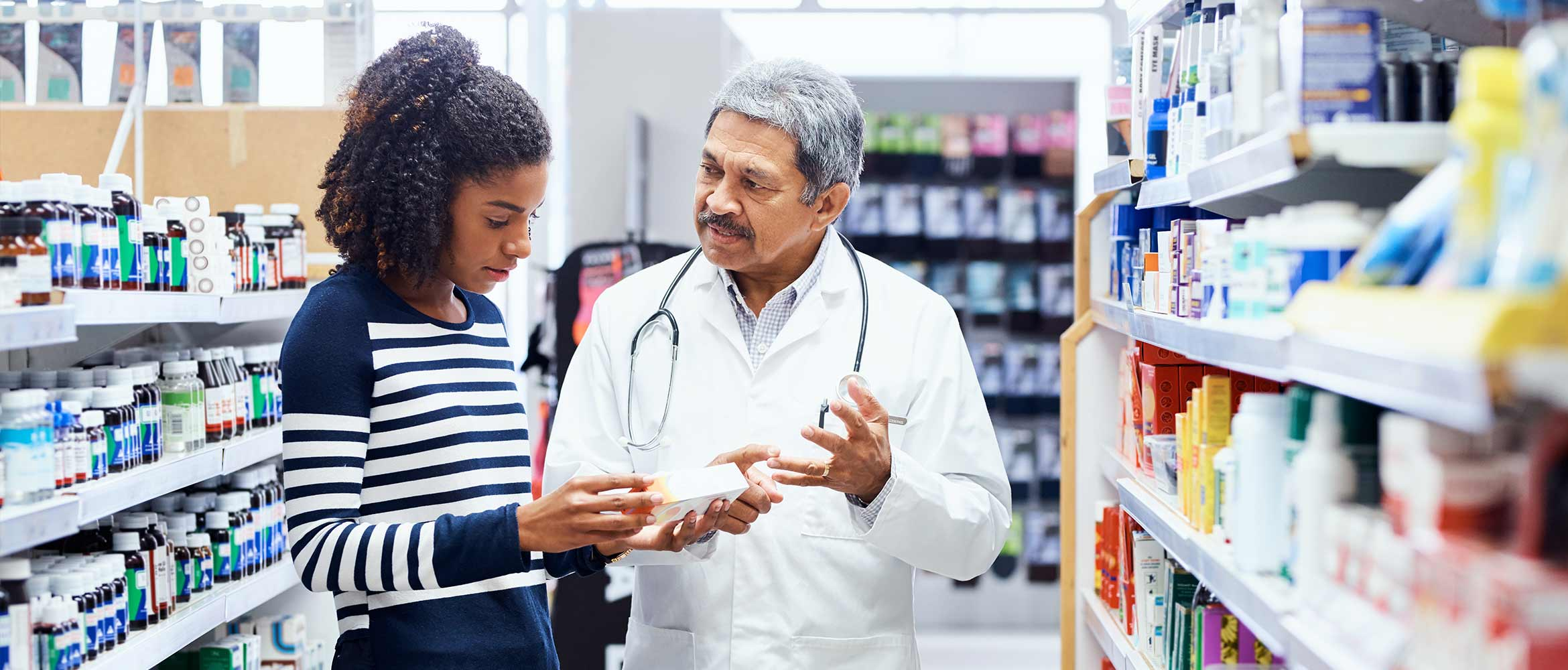 a pharmacist offers help to a woman in the aisle of a pharmacy