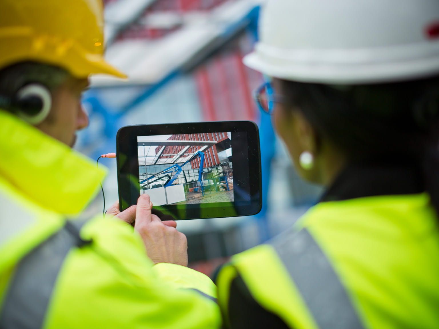 Two construction workers taking a photograph on site with a tablet device