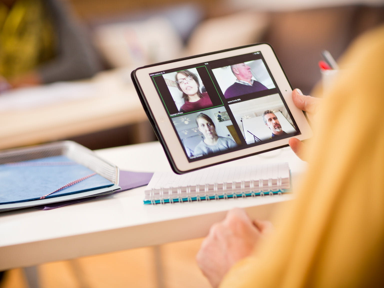 Woman using a tablet device to video conference with four people