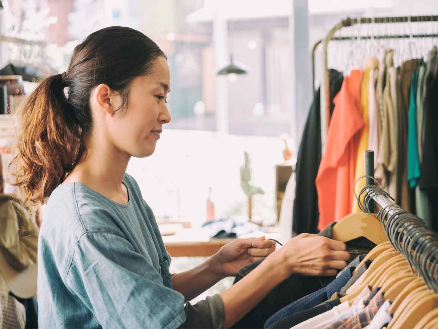 A young woman business owner works in her vintage clothing shop