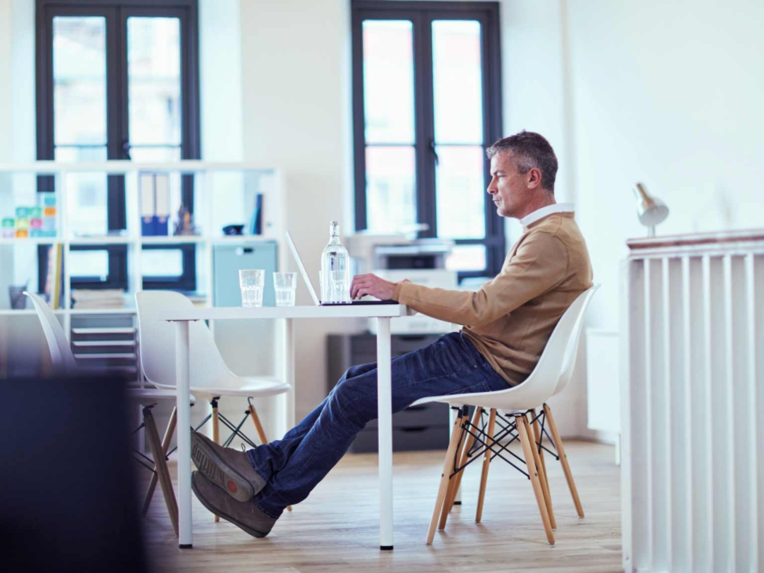 Man sat at a desk working on a laptop