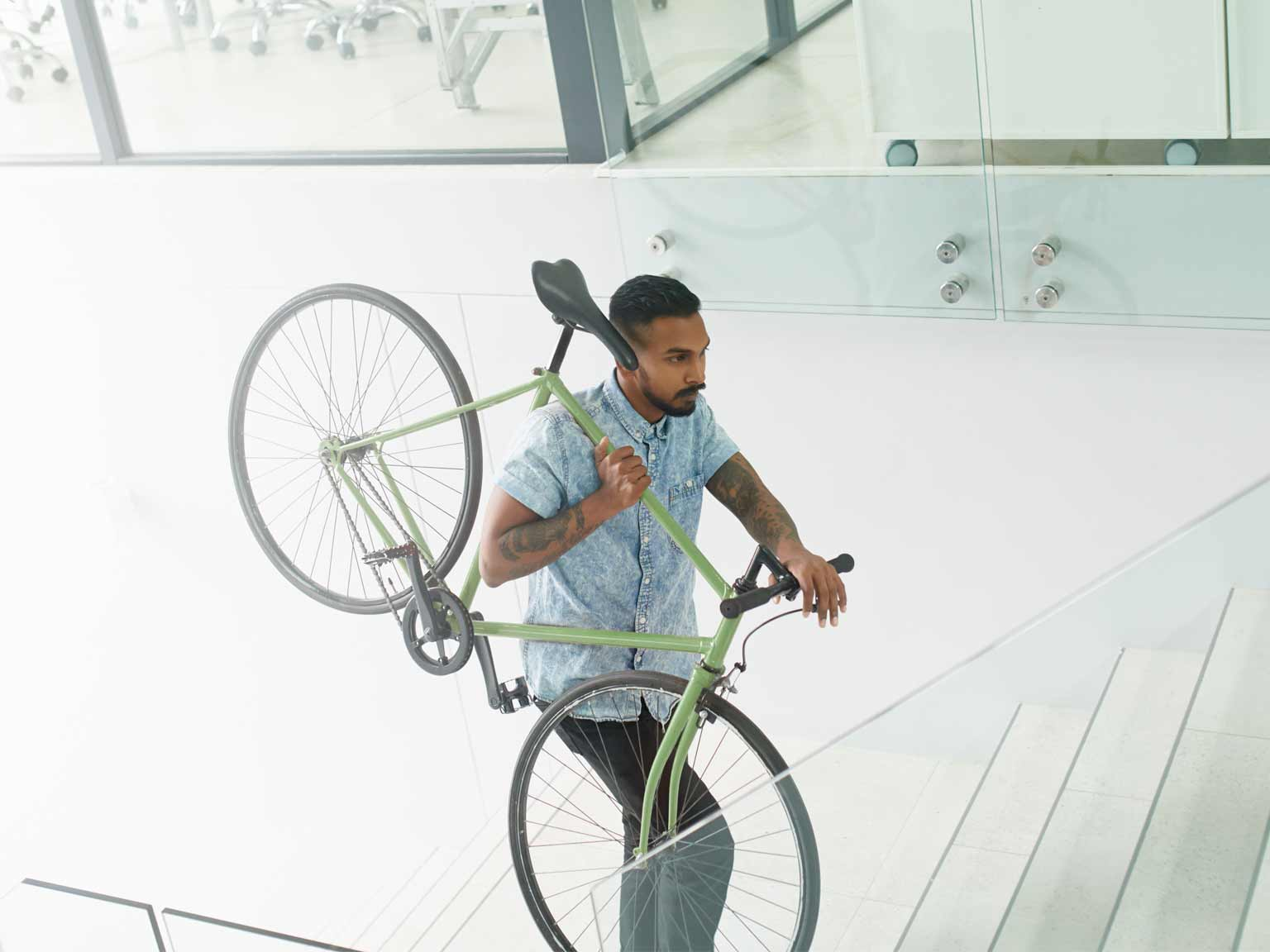 Man carrying a bike up the stairs
