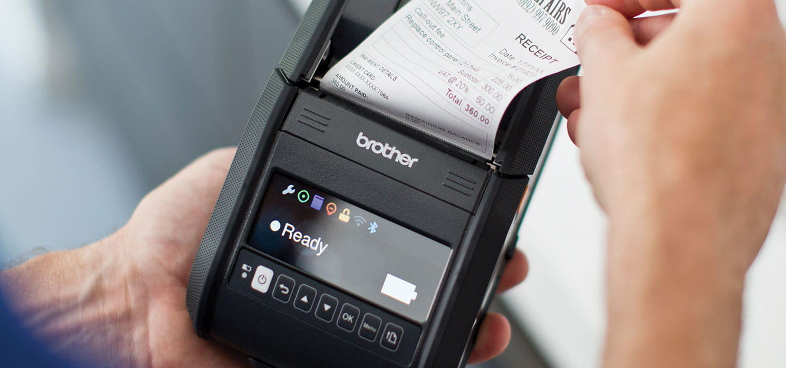 Person removing receipt from a handheld Brother mobile printer