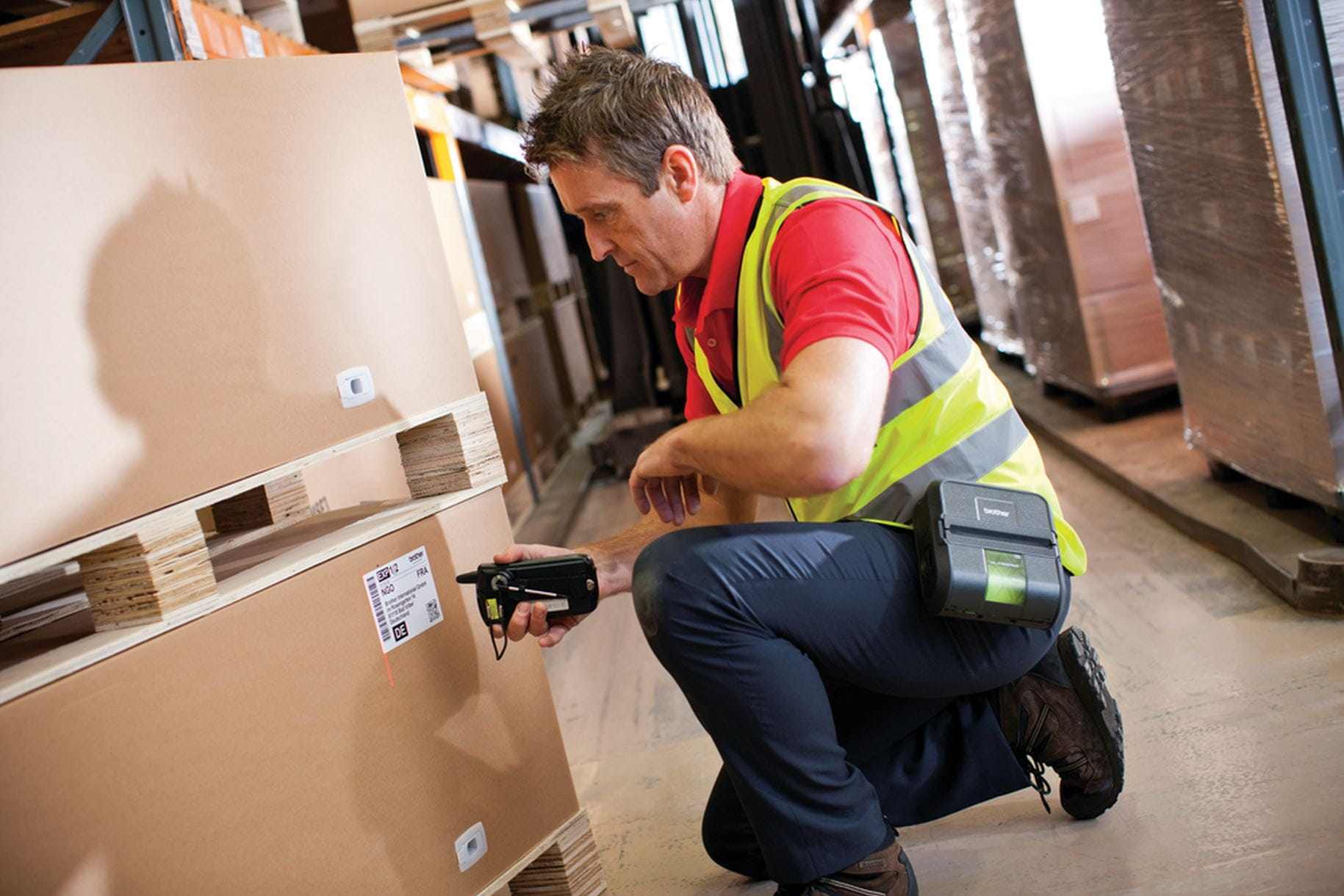 Warehouse worker scanning box label with RJ printer on belt clip