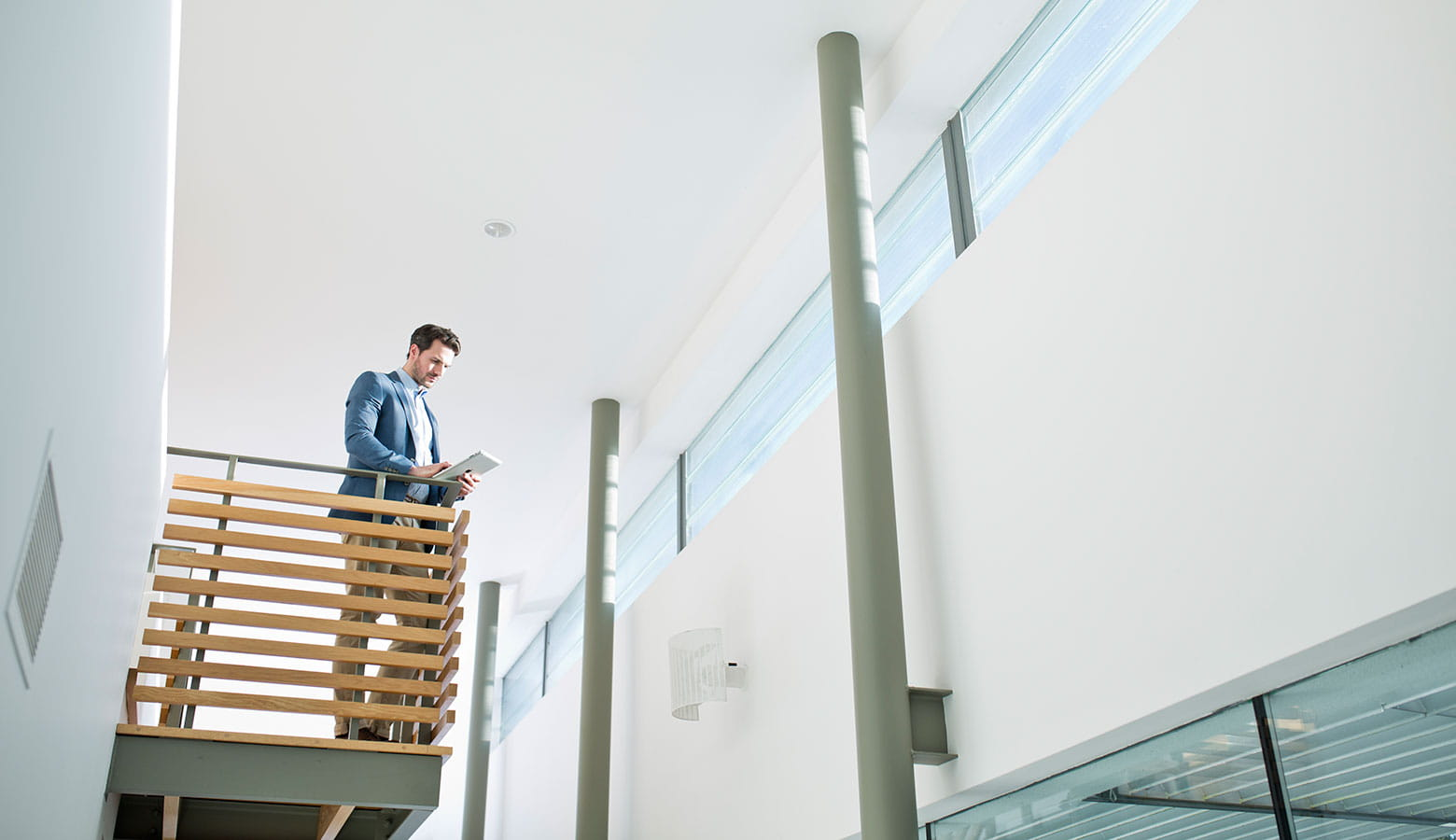 Businessman looking at tablet device while standing on balcony in office environment