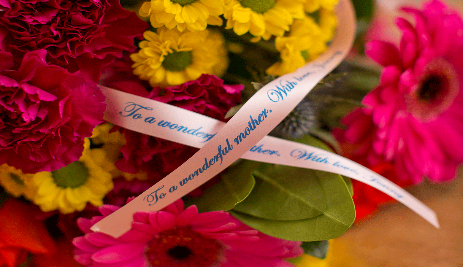 a bunch of flowers with the a pink ribbon