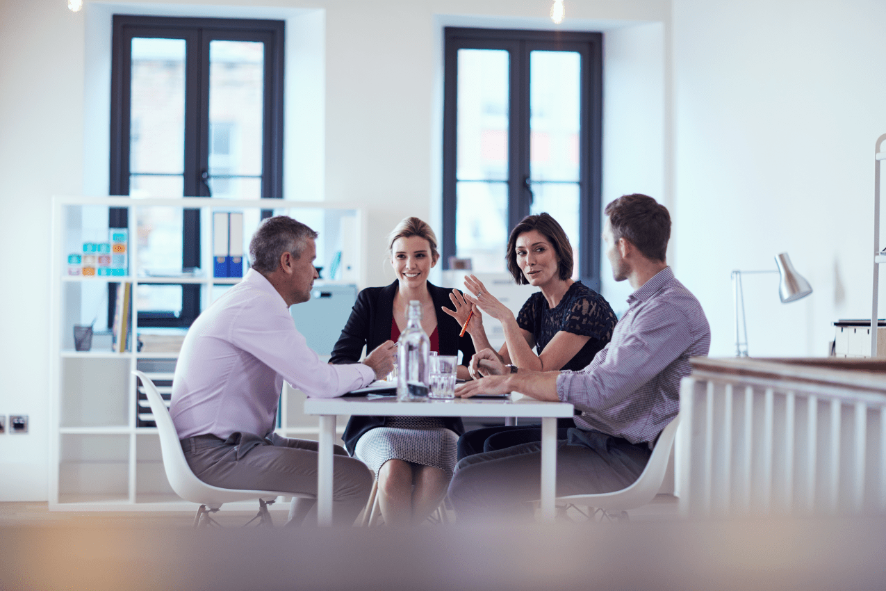 Four colleagues having a discussion around a table in an office environment