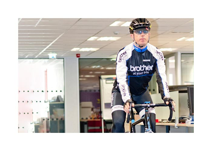 Phil Jones cycling through the Brother UK offices