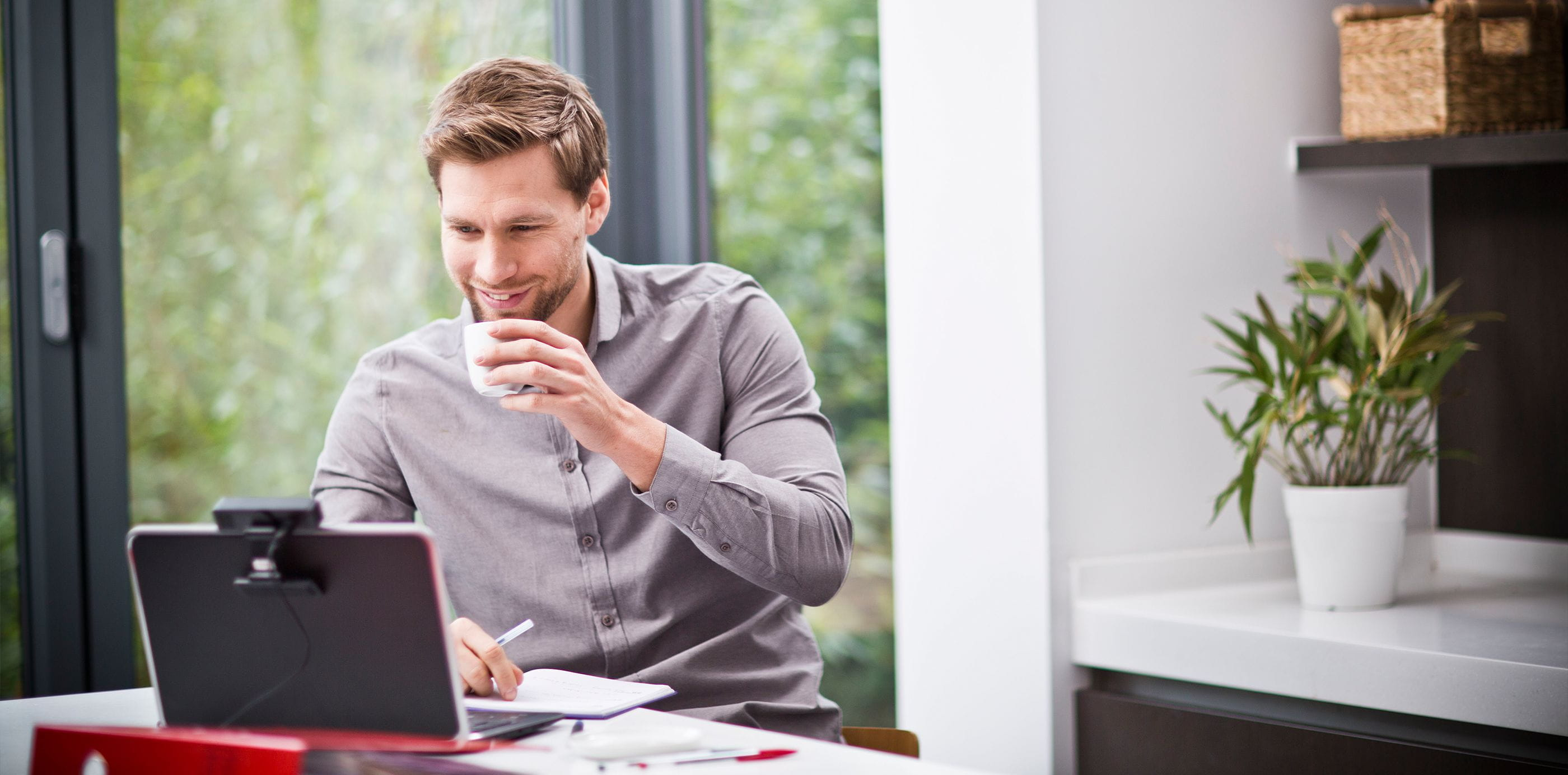Brother OmniJoin man working on laptop with webcam at home